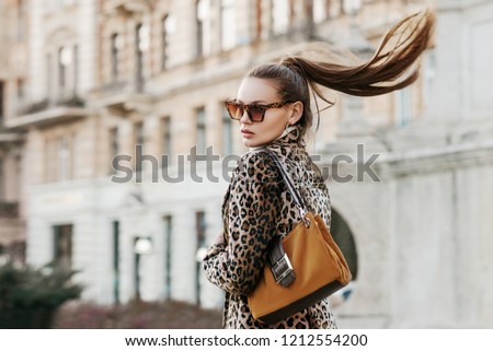 Outdoor close up fashion portrait of young beautiful fashionable woman wearing  sunglasses, leopard print blazer, holding brown suede bag, walking in street of european city. Copy, empty space #1212554200