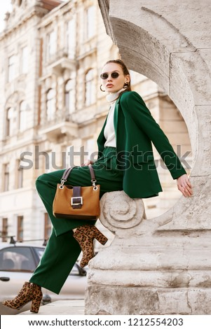 Outdoor full body fashion portrait of  fashionable woman wearing sunglasses, white turtleneck, green suit, blazer, trousers, leopard print boots, holding suede bag, posing in street of european city #1212554203