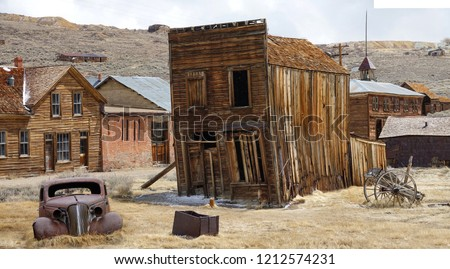 Rusty vintage car and idyllic wooden houses decay in the American wilderness after the gold rush. Scenic view of a ghost town in the Californian countryside slowly falling apart in rugged conditions. Royalty-Free Stock Photo #1212574231
