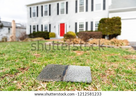 Front yard of house during day aftermath after storm roof tile shingle lying down on grass, damage closeup #1212581233