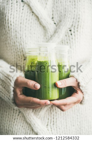 Winter seasonal smoothie drink detox. Female in light knitted sweater holding bottles of green smoothie or juice in her hands. Clean eating, weight loss, healthy dieting food concept #1212584332