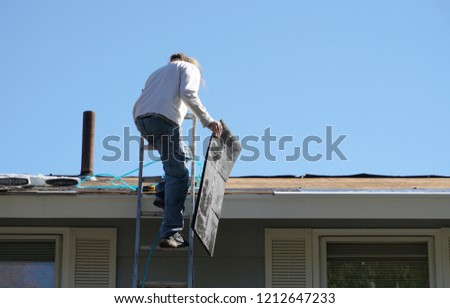 worker install new shingle on the roof of the house for roof repair #1212647233