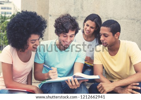 Team of laughing international students learning together outdoors on campus of university in summer #1212662941