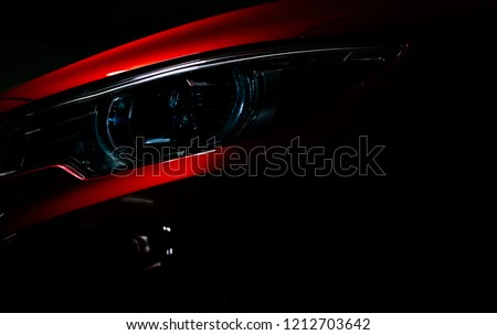 Closeup headlight of shiny red luxury SUV compact car. Elegant electric car technology and business concept. Hybrid auto and automotive concept. Car parked in showroom or motor show. Car dealership. #1212703642