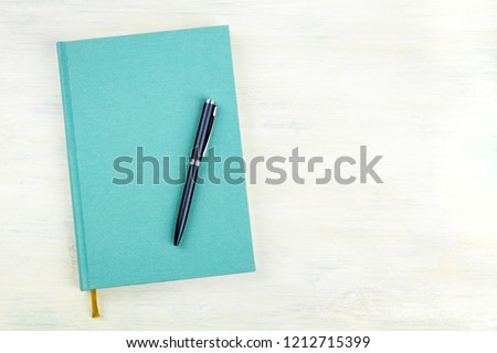 A photo of a teal blue journal with a pen, an elegant notebook or planner, shot from above with copy space #1212715399