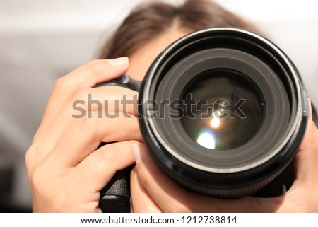 Female photographer with professional camera on blurred background, closeup #1212738814