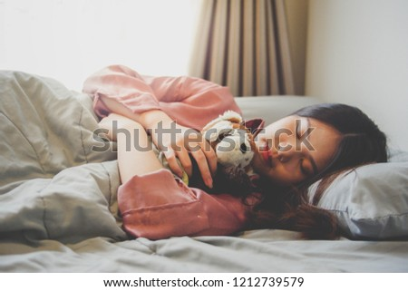 Image of an Asian woman sleeping and hugging a cute doll in bed with gray blanket , flare lighting from the window. #1212739579
