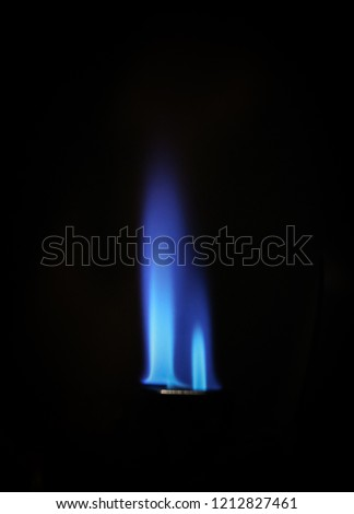 A close-up photograph of the flames from a jet lighter in front of a black background. This photo was taken in Brisbane, Australia.