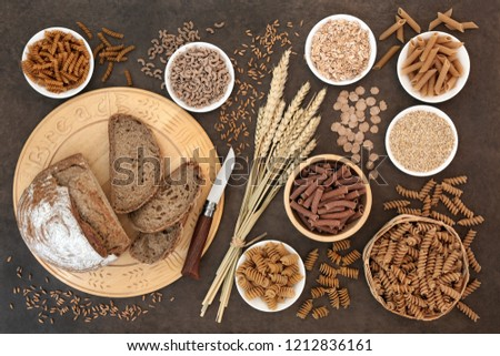 High fibre natural health food with whole wheat pasta, whole grain rye bread, oatmeal, oats, bran flakes and wheat sheath on lokta paper background.   #1212836161