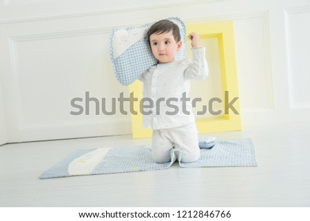 In the bedroom of the kindergarten, a cute little boy plays with his pillow. #1212846766