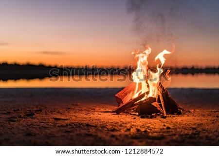Small campfire with gentle flames beside a lake during a glowing sunset. Western Australia, Australia. #1212884572