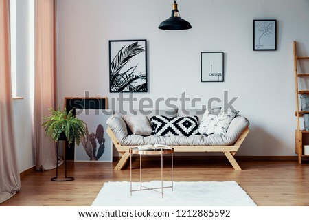 Patterned pillow on scandinavian sofa in stylish interior with gallery of poster, real photo #1212885592