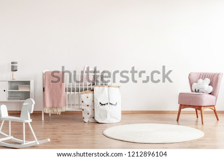 Bright scandinavian baby room with rocking horse, white nursery and pink armchairs, posters on the wall Royalty-Free Stock Photo #1212896104