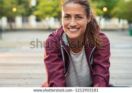 Portrait of smiling woman sitting on floor of city street after running. Healthy mature runner resting after workout exercise and looking at camera. Active sporty woman enjoying outdoors in autumn. #1212903181