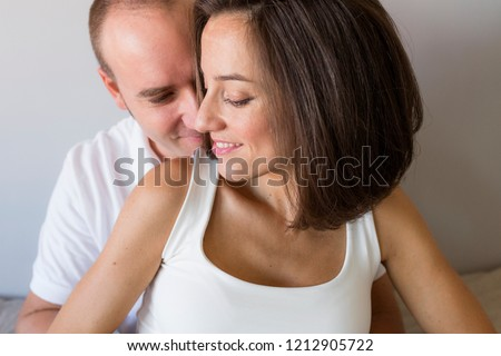 Beautiful pregnant woman and her handsome husband are hugging and smiling while spending time together. Love and couple lifestyle indoors #1212905722