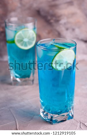 Delicious blue drink with a handful of lemon. Cocktail with limnom concrete background. Blue cocktail with lemon. #1212919105
