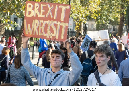 LONDON, UNITED KINGDOM - OCTOBER 20,  2018: Peoples' Vote March, demanding a second referendum on Brexit. Young man holding up placard reading 'Brexit Wrecksit' with another young man standing by him. #1212929017