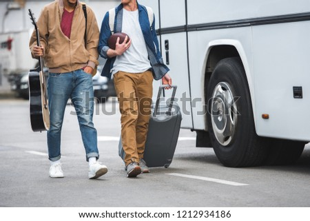 partial view of man with rugby ball carrying wheeled bag while his male friend walking near travel bus at street #1212934186