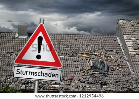 german Sturmschaden ( english translation: attention storm damage ) red warning sign in front of roof of house damaged by heavy hurricane tornado storm #1212954496