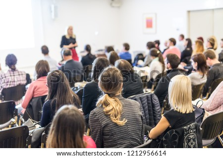 Business and entrepreneurship symposium. Female speaker giving a talk at business meeting. Audience in conference hall. Rear view of unrecognized participant in audience. Copy space on whitescreen. #1212956614