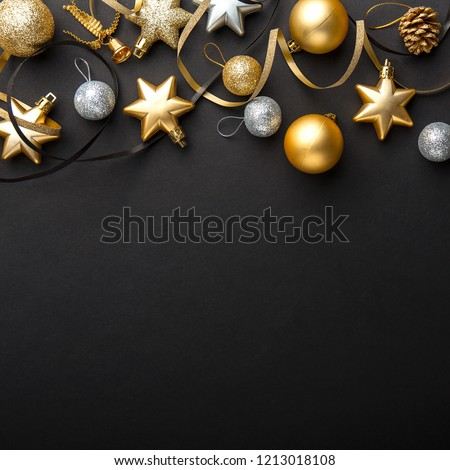 Beautiful christmas golden silver deco baubles on dark black background. Flat lay design. Copy Space. Square format.