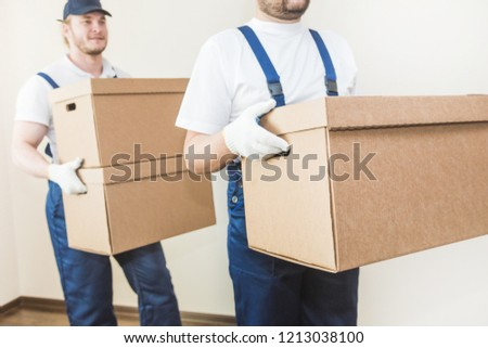Delivery man loading cardboard boxes for moving to an apartment. professional worker of transportation, male loaders in overalls #1213038100