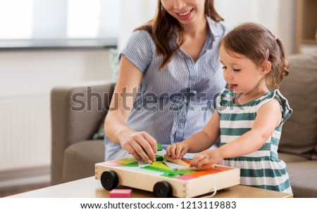 childhood and people concept - happy pregnant mother and little daughter playing with toy blocks at home #1213119883