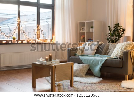 interior, christmas and interior concept - cushioned sofa, coffee table, garland string and candles on window sill in living room of cozy home #1213120567