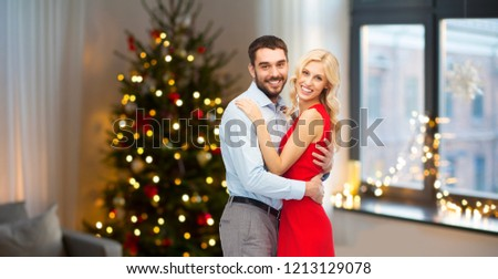 love and holidays concept - happy couple hugging over home room with christmas tree background #1213129078