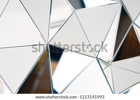 Mirror with crystals in wall, decoration and reflection. Abstract glass background. Polygonal surface. Close-up. Texture.