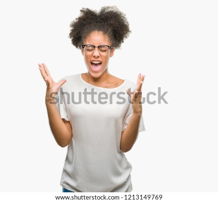 Young afro american woman wearing glasses over isolated background celebrating mad and crazy for success with arms raised and closed eyes screaming excited. Winner concept #1213149769