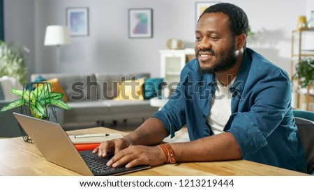 Handsome Smiling Black Man Using Laptop While Sitting at the Desk of His Cozy Living Room. #1213219444