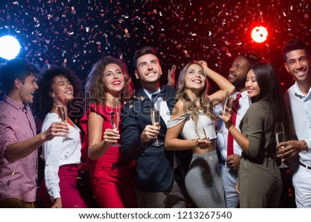 Cheerful friends with champagne flutes dancing at New Year party, smiling upwards at camera #1213267540