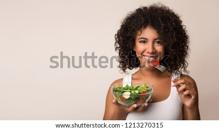African-american woman eating vegetable salad over light background with copy space Royalty-Free Stock Photo #1213270315