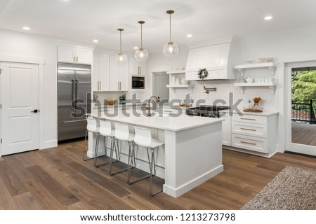 beautiful white kitchen in new luxury home with island, pendant lights, hardwood floors, and stainless steel appliances  #1213273798