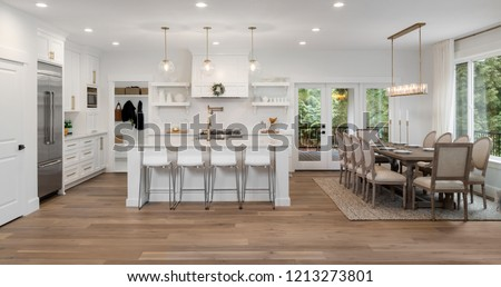 Beautiful panorama of white kitchen and dining room in new luxury home, with pendant lights, dining room table and chairs, kitchen island, and counters #1213273801