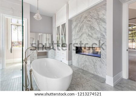 Elegant bathroom with fireplace and bathtub in new luxury home #1213274521