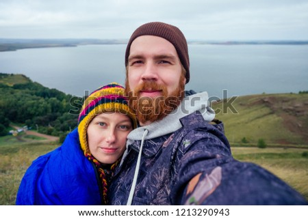 Selfie tourist bearded red-haired man hiker in a hat with a beloved woman taking self-portrait picture at lake. couple in love backpacker smiling at camera phone on adventure nature travel.