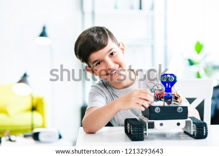 Cheerful smart schoolboy sitting at the table and constructing a robotic device at home #1213293643