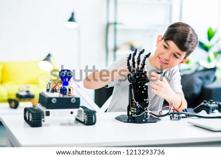 Nice optimistic smart boy testing his robotic device while beign involved in engineering classes #1213293736