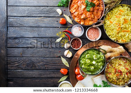 Different bowls with assorted indian food on dark wooden background, top view. Dishes and appetizers of indian cuisine. Chicken, curry rice, lentils, paneer, chapati and spices. #1213334668