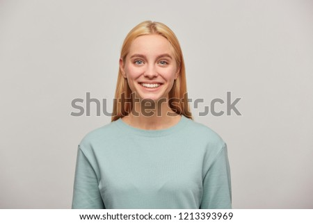 Close up of a lovely blonde young girl with long hair down, looking happy glad smiling, wearing blue casual sweatshirt, isolated over grey background #1213393969