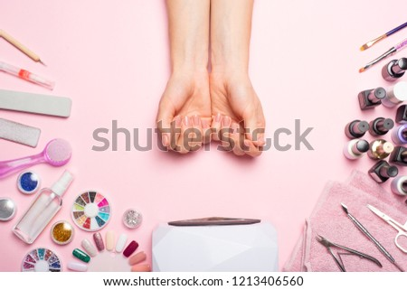 Nail care. beautiful women hands making nails painted with pink gentle nail polish on a pink background. Women's hands near a set of professional manicure tools. Beauty care #1213406560