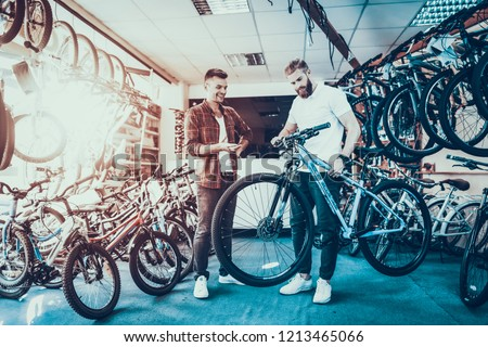 Consultant Shows Bicycle to Client in Sport Shop. Portrait of Young Shop Assistant Wearing White T-Shirt Helps in Mountain Bike Choosing. Happy Salesman in Sport Store with Row of Bikes on Backround #1213465066