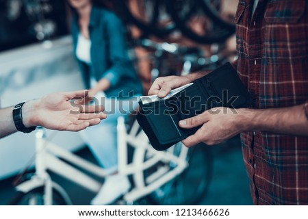 Closeup of Male Hand Gives Money From Purse to Seller. Shop Assistant Hand Takes Cash with Blurred Customers and Bikes on Backround in Sport Bicycle Store. Cash Payments Concept Royalty-Free Stock Photo #1213466626