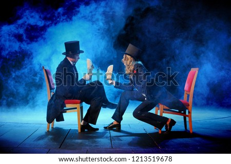young actors in tuxedos holding theatrical masks Royalty-Free Stock Photo #1213519678
