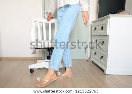 Beautiful Woman Wearing White Shirt and Blue Jeans Isolated. Portrait of Female Standing with White Chair Isolated at White Room Background #1213522963