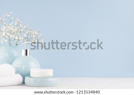 Bathroom interior - ceramic accessories - light blue circle vase with white flowers, soap dispenser , fluffy towels on white wood table.  #1213534840