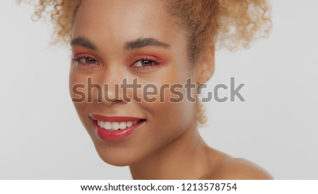 closeup portrait of mixed rase woman with red makeup in studio close up smiling and watching to the camera #1213578754