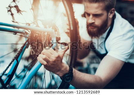 Handsome Bike Mechanic Repairs Bicycle in Workshop. Closeup Portrait of Young Bearded Man Wearing White T-Shirt Fixes Modern Cycle Transmission System. Bike Maintenance and Sport Shop Concept #1213592689